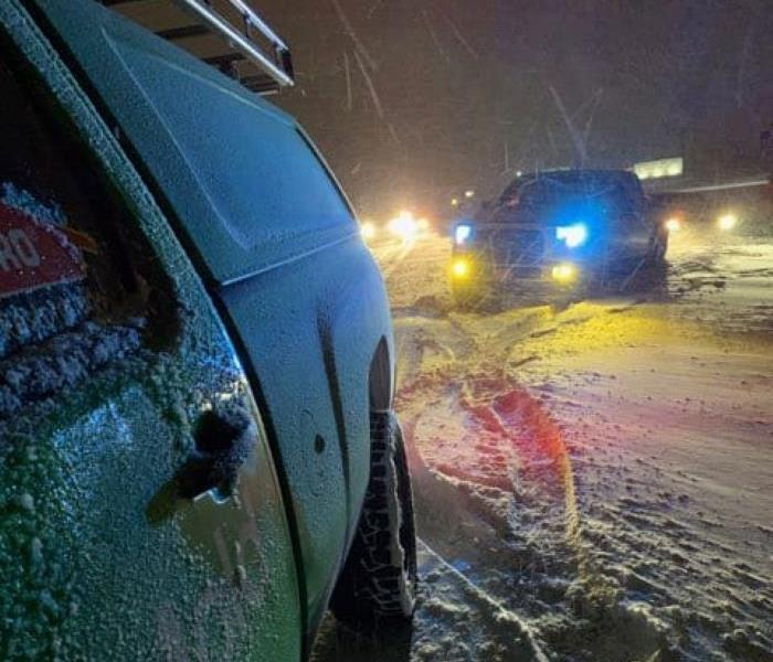 SERVPRO vehicle helping a car stuck in the snow